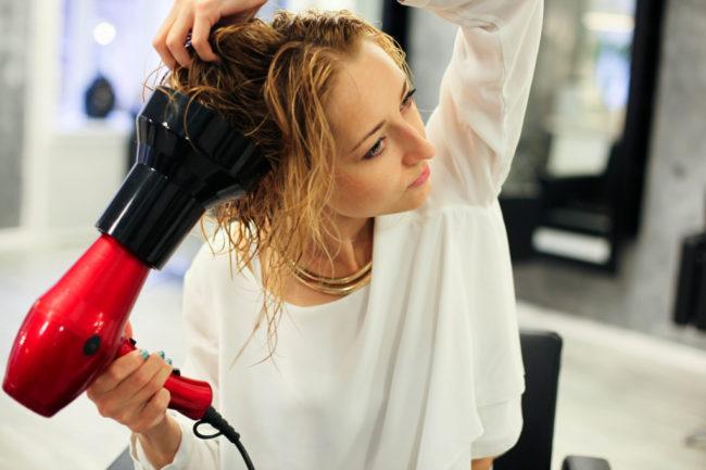 Девушка сушит волосы феном с диффузором